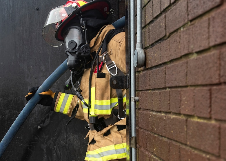 A U.S. Air Force firefighter assigned to the 48th Civil Engineering Squadron exits a structural training facility after completing a controlled burn training exercise at Royal Air Force Lakenheath, England, July 8, 2020. Liberty Wing firefighters participate in live fire and smoke training quarterly to ensure readiness for real-world situations. (U.S. Air Force photo by Airman 1st Class Jessi Monte)