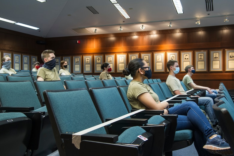Air Force Reserve trainees sit in a room wearing face coverings