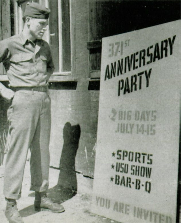 The 371st Fighter Group celebrated its second anniversary in Germany in July, 1945.  Here a unit member looks on to an advertisement for the festivities.   (The Story of the 371st Fighter Group in the E.T.O.)