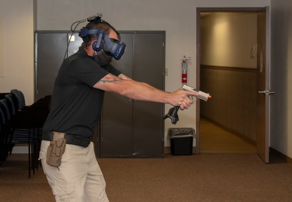 Brandon Feldman, 60th Security Forces Squadron training instructor, demonstrates virtual reality technology during Leadership Rounds July 10, 2020, at Travis Air Force Base, California. The 60th SFS uses this system to train and evaluate Airmen on use-of-force law enforcement technique. The Leadership Rounds program provides 60th AMW leadership an opportunity to interact with Airmen and get a detailed view of each mission performed at Travis AFB.  (U.S. Air Force photo by Heide Couch)