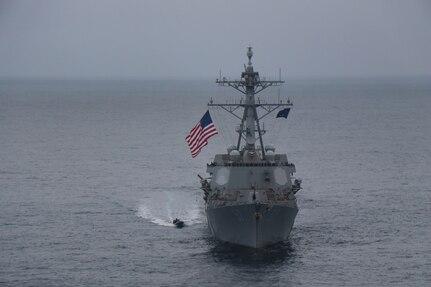 A rigid-hull inflatable boat comes alongside USS Halsey.