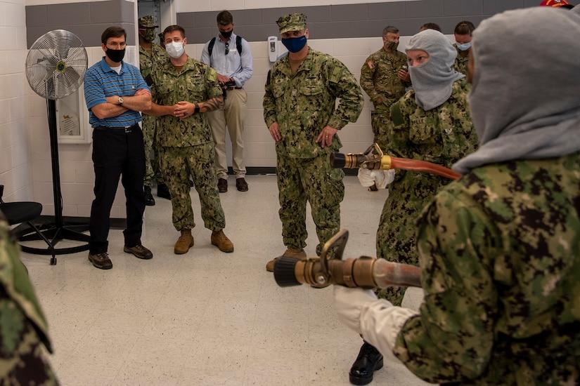 Sailors in firefighting gear wield hoses.