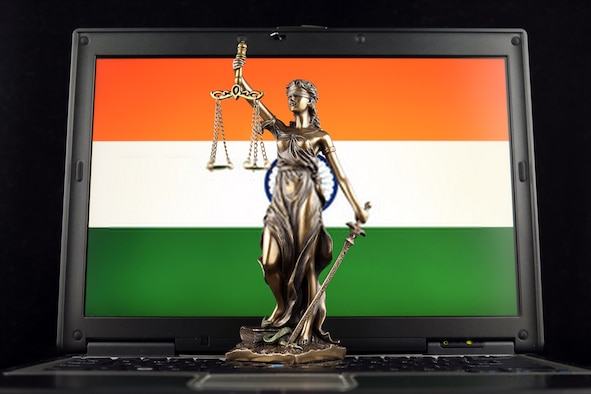 Lady Liberty stands before a digital display of the Indian flag.