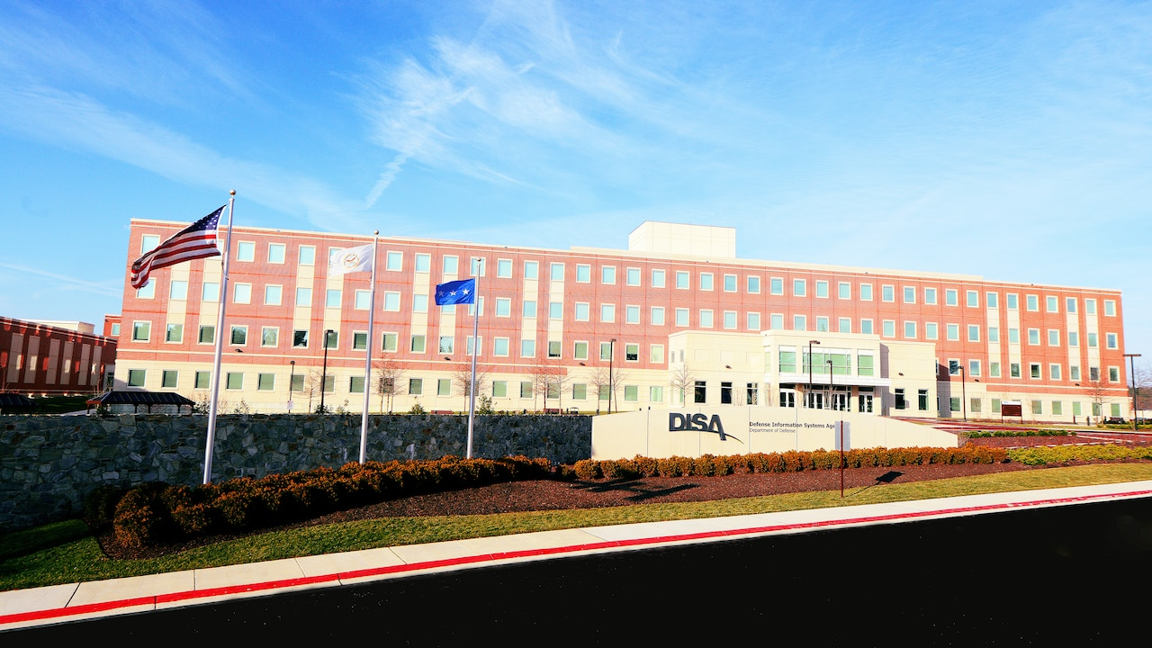 "A brick building sits under a blue sky. In front, a wall is inscribed with ""DISA"" and ""Defense Information Systems Agency."""