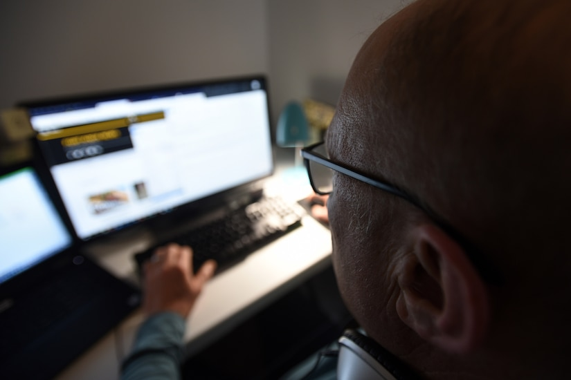 A man uses a computer in his home.