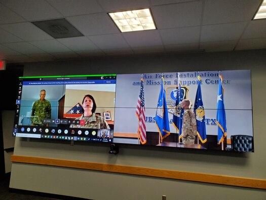 Photo of Brig. Gen. Patrice Melancon singing national anthem as Brig. Gen. John Allen and Maj. Gen. Tom Wilcox look on.