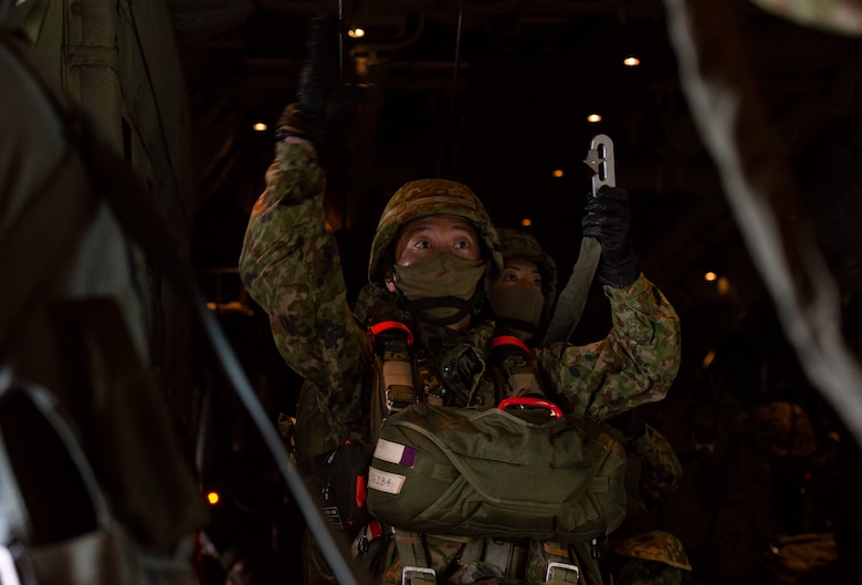 A Japan Ground Self Defense Force paratrooper hooks his parachute to a static line aboard a C-130J Super Hercules