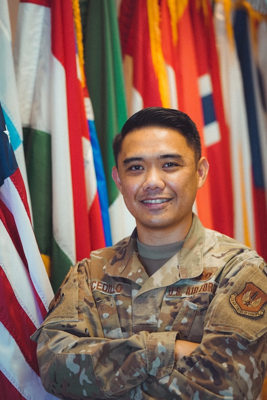 U.S. Air Force Master Sgt. Alexander Cedillo, 52nd Fighter Wing protocol specialist, poses in front of an arrangement of flags at Spangdahlem Air Base, Germany, May, 2020. Cedillo manages high-visibility visits across the 52nd FW and surrounding geographically separated units and advises leadership regarding protocol engagements within the U.S. and international affairs. (Photo courtesy of Master Sgt. Alexander Cedillo)