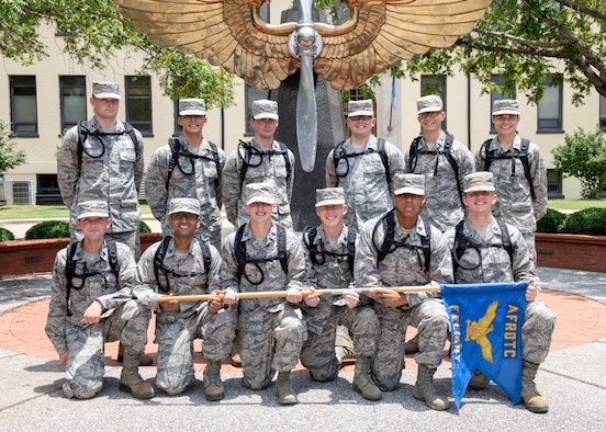 Air Force Reserve Officer Training Corps flight poses for a photo in front of the prop and wings statue outside of the Air University Headquarters building