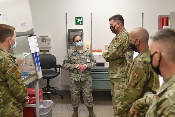 Photo shows an individual standing in front of lab testing equipment while explaining its use to a group of individuals.