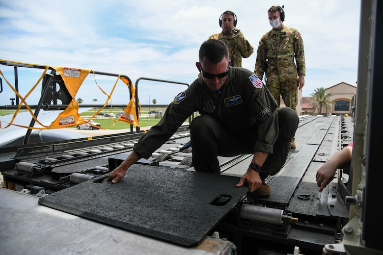 Senior Master Sgt. Aaron McLaughlin, 18th Air Refueling Squadron inflight refueler assigned to McConnell Air Force Base, Kansas places a cargo loader bridge plate prior to patient offload July 11, 2020, at Patrick Air Force Base, Florida. In preparation for the first operational aeromedical evacuation mission, three separate aeromedical evacuation's were simulated to help determine the usability of medical equipment, capacity of patients and proper aircraft staging. (U.S. Air Force photo by Airman 1st Class Nilsa Garcia)
