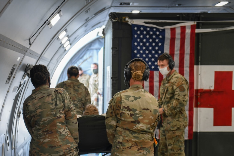 Photo of Airmen offloading a non-ambulatory patient