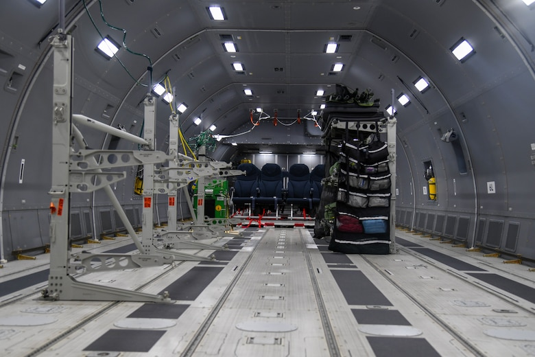 Litter stations stand assembled in the fuselage of a KC-46A Pegasus prior to patient arrival July 10, 2020, at Joint Base Andrews, Maryland. Prior to the mission, the aircraft was configured to support patient movement. A litter stanchion augmentation set container was secured on the aircraft  to store the equipment required to build up to nine litter stations. (U.S. Air Force photo by Airman 1st Class Nilsa Garcia)