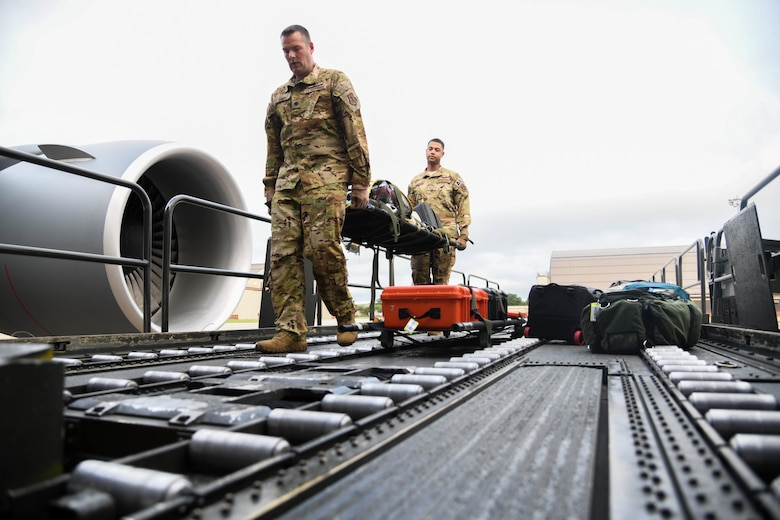 Lt. Col Jason Arndt, 133rd Airlift Wing flight nurse assigned to the Minnesota Air National Guard Base and Staff Sgt. Jeremy Gregory, 145th Airlift Wing aeromedical evacuation technician assigned to the North Carolina Air National Guard Base, carry a litter containing in-flight medical equipment July 10, 2020, at Joint Base Andrews, Maryland. The mission originated at Joint Base Andrews and transited a total of five patients and two attendees to Naval Station Norfolk, Virginia; Patrick AFB, Florida; and Travis AFB, California. (U.S. Air Force photo by Airman 1st Class Nilsa Garcia)