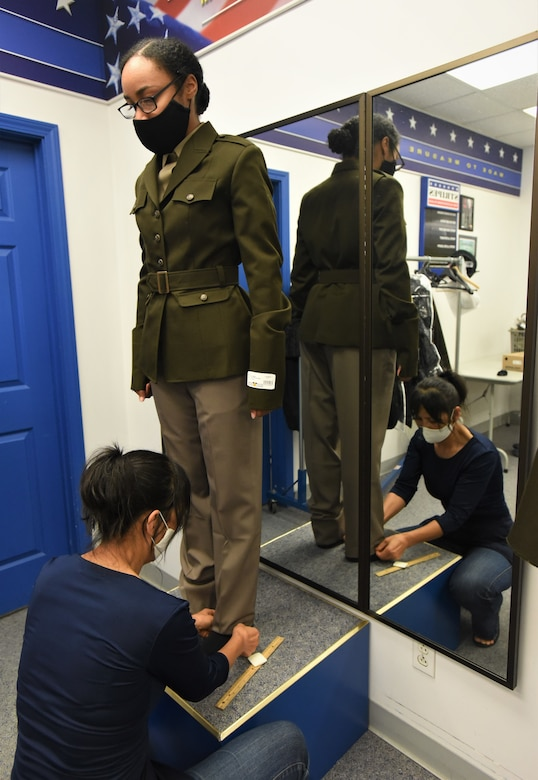 female in a uniform being measured by a tailor.