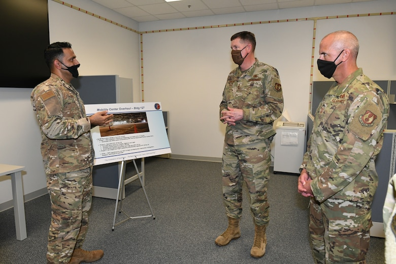 Photo shows three individual standing and speaking to each other in front of an easel.