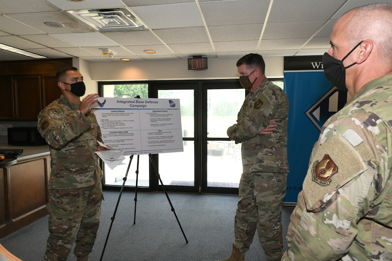 Photo shows three individuals speaking in front of an easel.