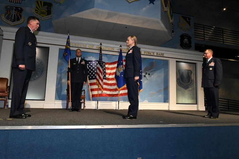 Photos shows four individuals on a stage with one holding the guidon and the other three performing the change of command.