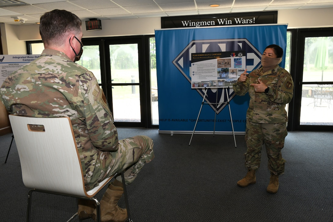 Photo shows one individual sitting in a chair listening to a briefing given by another individual in front of an easel and banner.