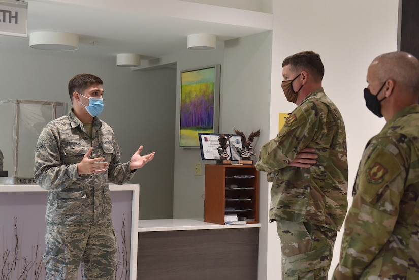 Photo shows an Airman speaking to the general and chief in front of the Public Health check in.