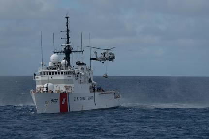 A navy helicopter transfer suspected contraband from a U.S. Coast Guard Cutter.