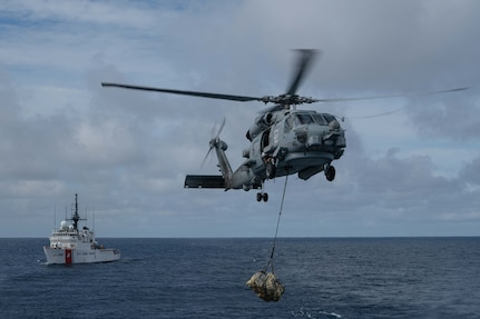 A U.S. Navy helicopter transfer suspected contraband from a U.S. Coast Guard Cutter.