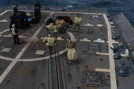 U.S. Sailors and Coast Guardsmen on USS Halsey  move suspected contraband on the flight deck.