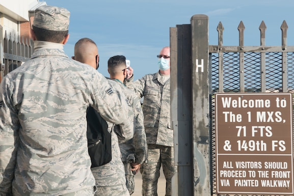 Airmen line up at a gate opening waiting to have their temperature checked
