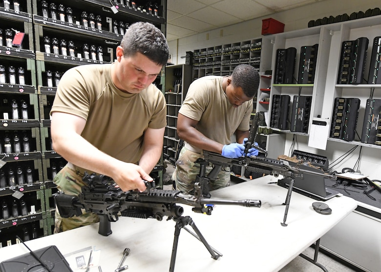 Senior Airman Keith Talbot, 9th Security Forces Squadron combat arms instructor (left), and Staff Sgt. Ansumana Turray, 9th SFS assistant NCOIC of combat arms, inspect M249 Light Machine Guns, June 26, 2020, at Beale Air Force Base California. Recce Town's combat arms instructors conduct weapon inspections regularly to ensure they are in working condition. (U.S. Air Force photo by Airman 1st Class Luis A. Ruiz-Vazquez)