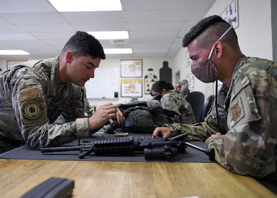 Tech. Sgt. Chad Choker, NCOIC of combat arms (left), assists a student during a Combat Arms Training and Maintenance course, June 22, 2020, at Beale Air Force Base, California. CATM instructors teach Airmen how to properly use, disassemble, and clean a weapon safely. (U.S. Air Force photo by Airman 1st Class Luis A. Ruiz-Vazquez)
