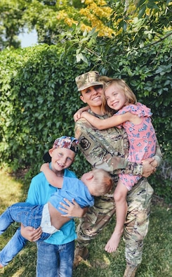 Airman 1st Class Sarah Johnson, an F-3 weapons loader, takes a moment to pose with her children
