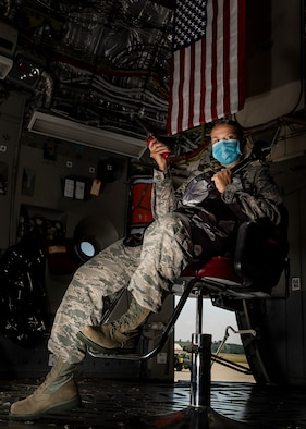 Senior Airman Sara Gutherie, 911th Aircraft Maintenance Squadron integrated flight control systems mechanic, poses for a photo inside a C-17 Globemaster III with a wrench and hair clippers while wearing an apron and personal protective equipment at the Pittsburgh International Airport Air Reserve Station, Pennsylvania, July 8, 2020. During COVID-19 restrictions, Gutherie helped her fellow Airmen by using her skills as a licensed cosmetologist to give them haircuts to ensure they stayed within regulations while taking donations for the Needy Airman Fund in return. (U.S. Air Force photo by Joshua J. Seybert)