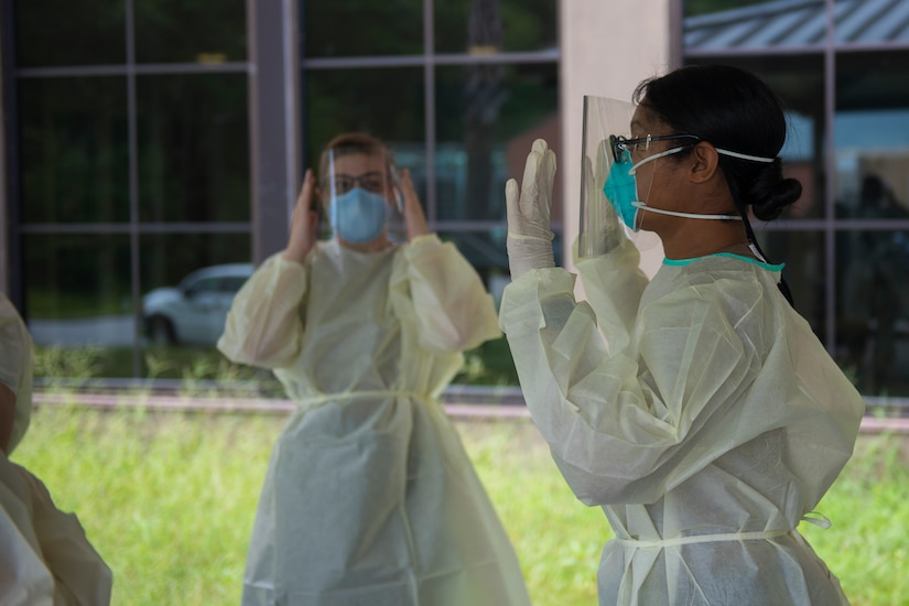 Hospital Corpsman Petty Officer 1st Class Shamace Phillips, a preventative medicine technician assigned to the Navy Medicine Readiness and Training Command, demonstrates the correct way to wear the personal protective equipment that is used to test patients for COVID-19 on July 8, 2020, at the Naval Health Clinic Charleston on Joint Base Charleston, S.C. Hospital Corpsmen from the NHCC were tasked with learning how to administer a COVID-19 swab test. The training will be used to test symptomatic patients and Sailors, as well as asymptomatic Sailors to attempt to lessen the spread of the virus.