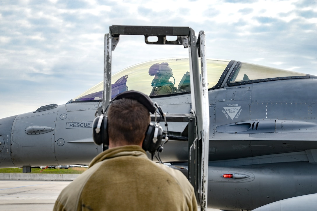 A photo of Senior Airman Colin F. Beebe preparing to install a ladder onto an F-16.