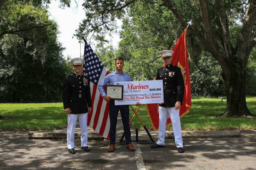Lt. Col. Mark Lenzi, commanding officer, Recruiting Station Tampa, poses for a photo with Ryan Thompson, an Edgewater High School graduate, after receiving his Naval Reserve Officers Training Corps scholarship check, June 26, 2020, Tampa, Fla. Ryan emulates the fighting spirit that Marines have and was selected based off his overall character in his community and at home and has earned $180,000 in scholarship funds. Ryan is scheduled to attend Arizona State University in the fall. (Official Marine Corps photo by Sgt. Calvin Shamoon/ released)