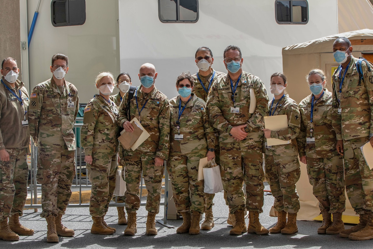 Members of a military medical task force wearing face masks and camouflage uniforms pose for a group photo. Some hold file folders.