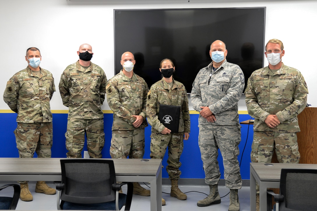 A photo of Master Sgt. Jennifer L. Hall posing for a photo with other Airmen after her virtual graduation from the First Sergeant Academy.