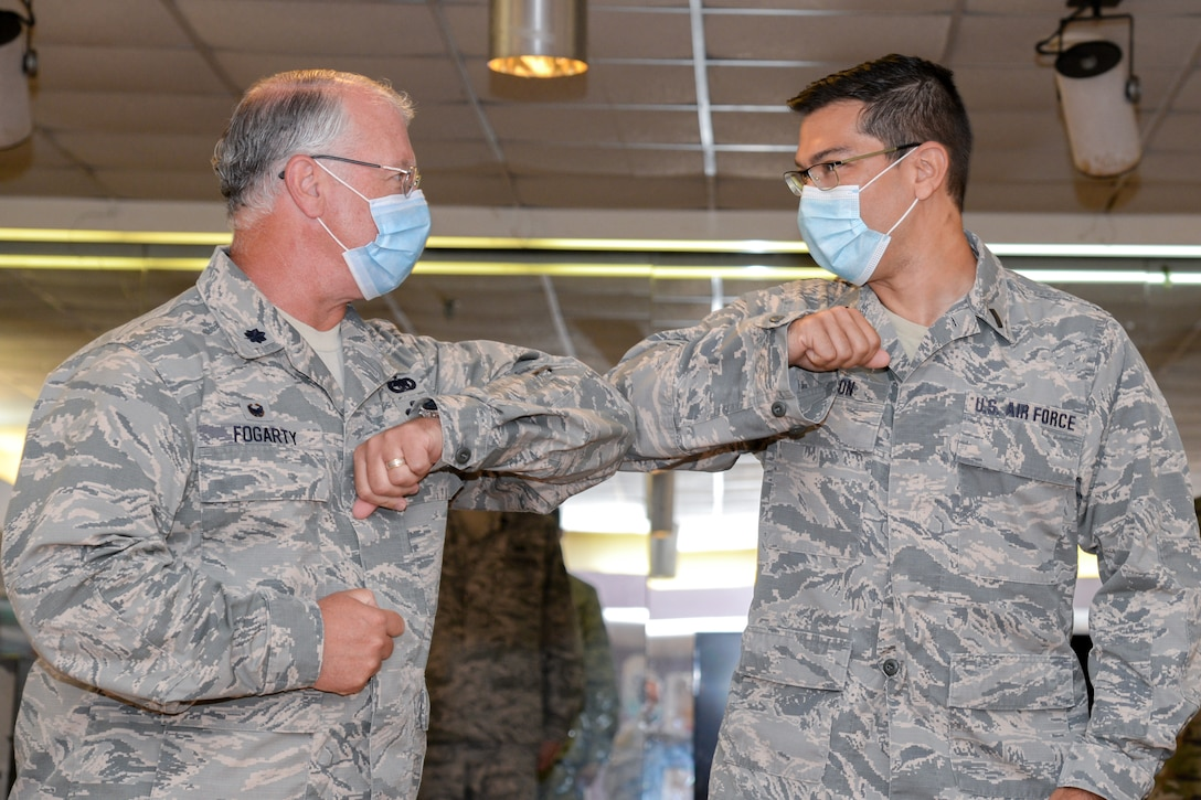 A photo of 1st Lt. Edwin Cintron II bumping elbows with Lt. Col. John J. Fogarty III.