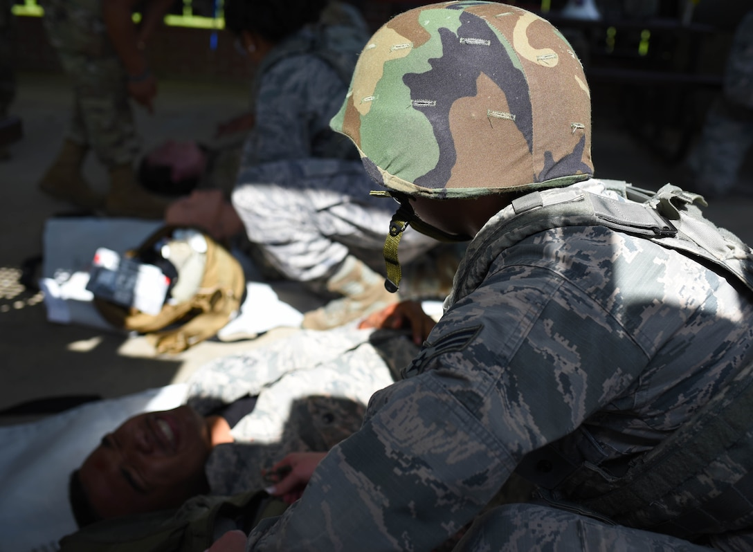 A 14th Medical Group Airman treats a 'wounded' actor in a simulated battlefield during the Tactical Combat Casualty Care All Combatants course July 16, 2020, at the Kortiz Clinic on Columbus Air Force base, Miss. The event challenged medics to perform battlefield care in a simulated combat environment to help bolster their medical skills by performing on actors and dummies. (U.S. Air Force photo by Senior Airman Jake Jacobsen)