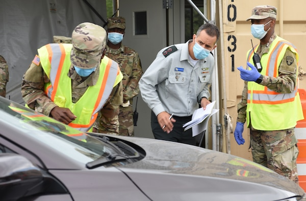 Lt. Col. Hai Rekah of the Israel Defense Forces Home Front Command, with members of the New York National Guard, observes intake procedures for motorists at the drive-thru test site at Glen Island Park in New Rochelle, N.Y., July 15, 2020. Rekah was in New York to meet with New York National Guard leaders to see parts of New York's response to COVID-19, as Israel's Homefront Command responds to the pandemic.