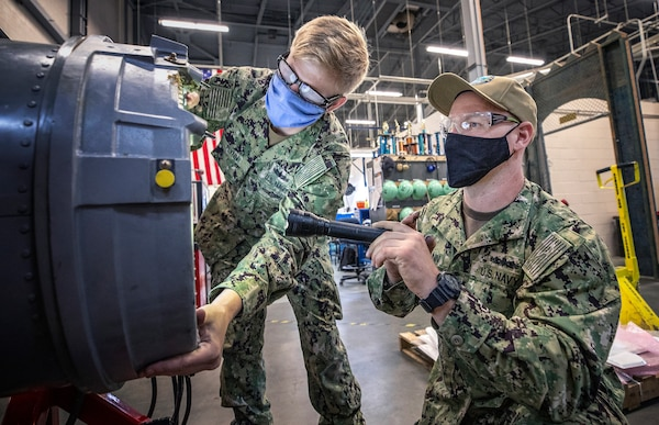 Gunner's Mate 1st Class Joshua Heitmann, right, a SurgeMain Sailor, practices installing a drum cover on a Close-In Weapons System mock-up with Fire Controlman 1st Clastt Kevin Flynn in the Shop 38 Gun Shop, July 15, 2020 at Puget Sound Naval Shipyard & Intermediate Maintenance Facility Detachment Everett.