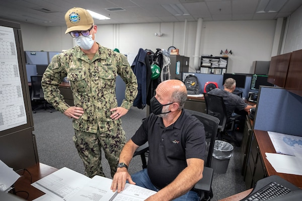 Electrician's Mate 1st Class Cory Bonacorsi, left, a newly-arrived Surge Main Sailor, talks with Steven Hall, Code 210.3 engineer, July 15, 2020 in the office at Puget Sound Naval Shipyard & Intermediate Maintenance Facility Detachment Everett.
