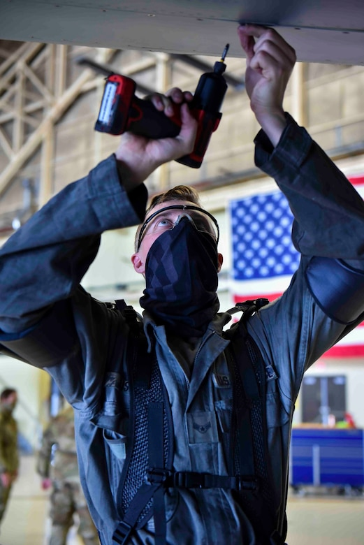 Airman 1st Class Avery Justice, 92nd Maintenance Squadron crew chief, removes screws from the bottom of a KC-135 Stratotanker wing while wearing an exoskeleton apparatus at Fairchild Air Force Base, Washington, July 16, 2020. The exoskeleton apparatus is used to relieve pressure off of the shoulders and back of Airmen. (U.S. Air Force photo by Airman 1st Class Kiaundra Miller)