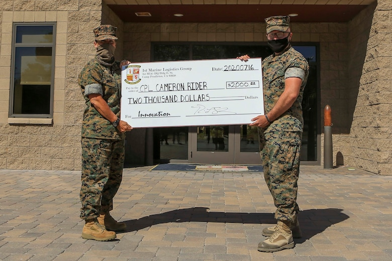 Commanding General of 1st Marine Logistics Group Brig. Gen. Bobbi Shea awards $2000 to the winner of 1st MLG Innovation Award, Cpl. Cameron Rider, a radio operator with Combat Logistics Regiment 1, for his design and fabrication of a vehicle-mounted antenna on Camp Pendleton, California, July 16, 2020. Rider utilized his previous experience and knowledge of constructing field-expedient antennas in his innovation of a low-cost, vehicle-mounted antenna capable of maintaining on-the-move communication. (U.S. Marine Corps photo by Lance Cpl. Ulises Salgado)