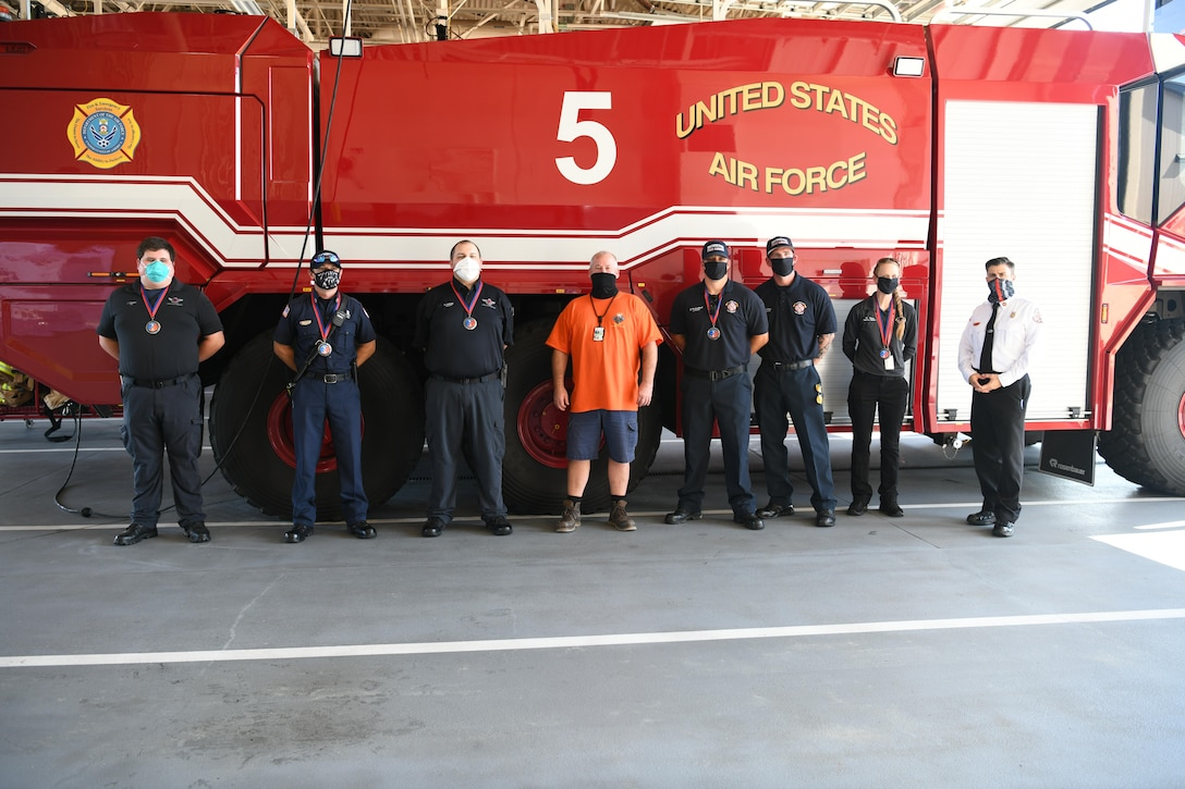 Photo of group standing in front of fire truck.