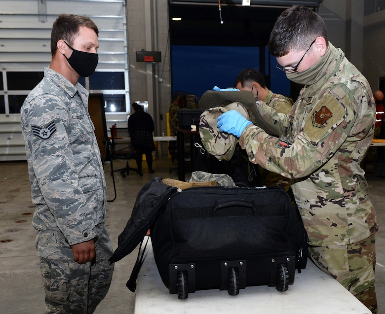 An Airman assigned to the 28th Logistics Readiness Squadron, Ellsworth Air Force Base, S.D., checks luggage as part of a mobility processing line in preparation for a Bomber Task Force deployment, July 13, 2020. Airmen from the 28th Bomb Wing deployed to the U.S. Indo-Pacific Command's area of responsibility to conduct Bomber Task Force missions, which help maintain global stability and security while enabling units to become familiar in different regions. (U.S. Air Force photo by Airman 1st Class Quentin K. Marx)