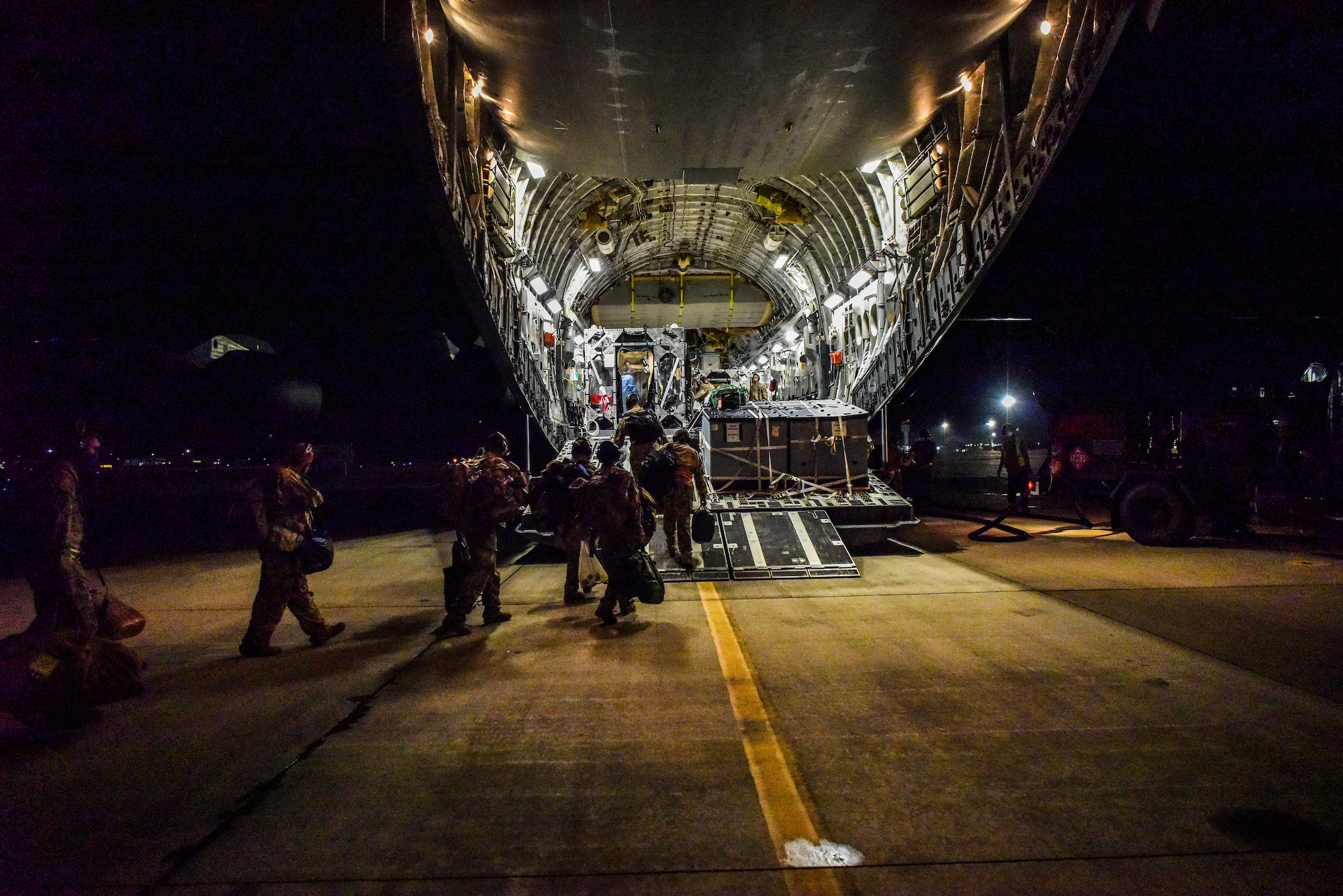Airmen from the 60th Air Mobility Wing support a Transport Isolation System operation at Joint Base Pearl-Harbor Hickam, Hawaii, July 17, 2020. Several U.S. Air Force units came together to rapidly deploy the bio-containment capability for the first time in the Indo-Pacific theater in support of a COVID-19 aeromedical evacuation mission. The TIS is an infectious disease containment unit designed to minimize contamination risk to aircrew and medical attendants, while allowing in-flight medical care for patients afflicted by a disease. (U.S. Air Force photo by Tech. Sgt. Anthony Nelson Jr.)