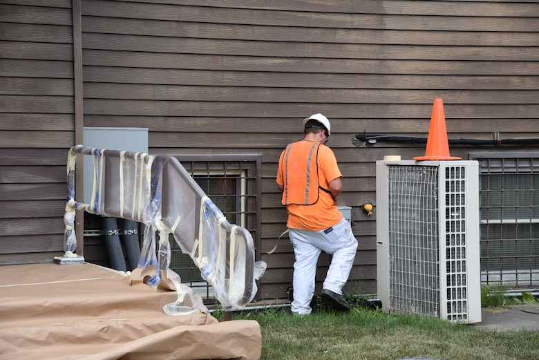 A worker tapes off equipment in preparation for painting the northeast side of the building.