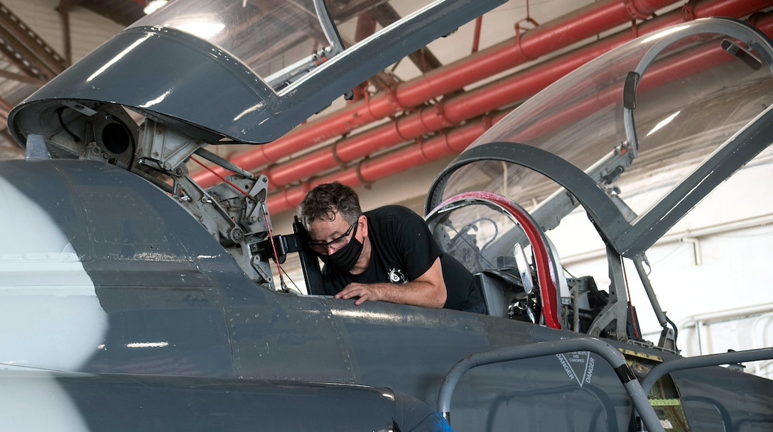 Tom Brewer, 12th Maintenance Squadron maintainer, wears a face mask as he repairs a T-38C seat hinge at Joint Base San Antonio-Randolph July 14.