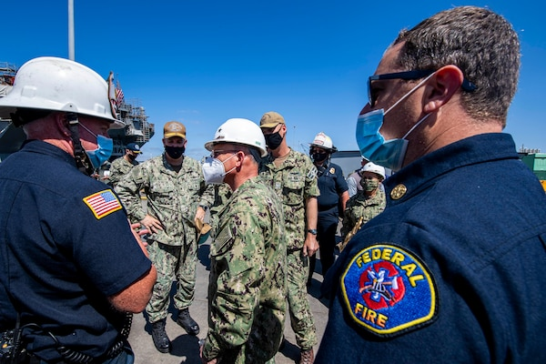 The Chief of Naval Operations (CNO) Adm. Mike Gilday speaks with federal firefighters on the pier next to the amphibious assault ship USS Bonhomme Richard (LHD 6).